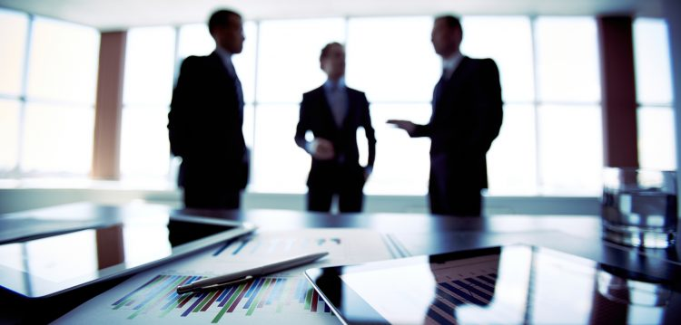 silhouette of three businessmen in a boardroom