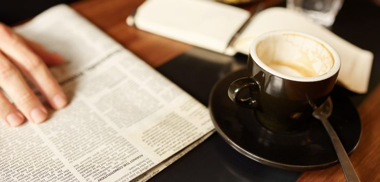 Newspaper and espresso cup